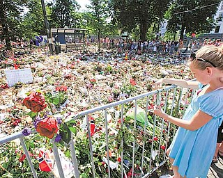 People are seen around thousands of flowers and tributes laid outside the Oslo Cathedral in Oslo, Norway in memory of the victims of July 22 bomb attack and shooting rampage, Sunday, July 31, 2011. Anders Behring Breivik, the 32-year-old Norwegian extremist, has confessed to setting off a car bomb that killed eight people in downtown Oslo and then gunning down scores of youth from the left-leaning Labor Party at their annual retreat on an island northwest of the capital. Sixy-nine of them died. (AP Photo/Lefteris Pitarakis)