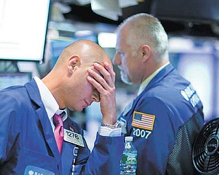 Traders show their frustration as they work on the floor of the New York Stock Exchange on Thursday. The Dow dropped 4.3 percent to close at 11383.68.