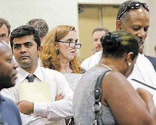 In this July 13, 2011 photo, attendees stand in lines that weave throughout a room filled with recruiting booths during a National Career Fairs job fair, in Dallas. The number of people seeking unemployment benefits dipped last week, a sign the job market may be improving slowly.(AP Photo/Tony Gutierrez)