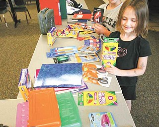 Cody Koellner, 10, and his sister, Colleen Koellner, 6, look over items they will be able to shop for at the Beautitude HouseÕs Òmock storeÓ at its administrative offices at 238 Tod Lane on the campus of St. Edward parish in Youngstown or at its location at 1370 Tod Ave. NW in Warren on Aug. 12. The deadline for donations is Wednesday..