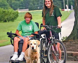 Jill Molnar, who has advanced multiple sclerosis, and her daughter, Megan Molnar, with Jill's constant companion, Odie, a yellow labrador retriever, at the Molnar Farm Market in Springfield Township, where Jill runs the cash register. Megan, a second-year occupational therapy student at Duquesne University in Pittsburgh, is riding this weekend in the 150-mile Ohio Bike MS Pedal to the Point event as team captain of Jill's Jaunters.
