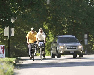 ROBERT K. YOSAY | THE VINDICATOR..A passing car gives the riders room as they head east on Sheridan (Midlothian is behind them)..Ride to work with Franko...Frank Krygowski-- White shirt -- Carl Frost - Orange and Black - Todd Franko in Orange -30-
