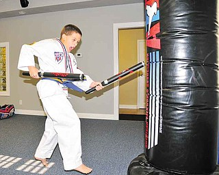 Tanner Craig, 8, of Austintown gets ready to leap into the air while striking a heavy bag at Austintown ATA Martial Arts.