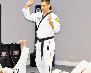 Louis Italiano leads a group of students in stretches during Monday's class at Austintown ATA Martial Arts. ATA will host a grand opening at its new location, 420 S. Canfield-Niles Road, from 10 a.m. to 3 p.m. today.