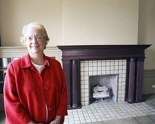 Constance Shaffer, retired executive director of the Youngstown YWCA, stands in front of a fireplace in the lobby of the YW building.