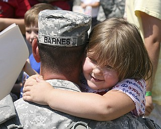 JESSICA M. KANALAS | THE VINDICATOR..Sgt. Chris Barnes of Norwolk embraces his daughter, Halle, 4, after stepping off the buses. .... -30-