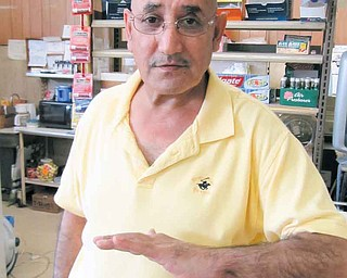 Mohammad Darwish, owner of the NorthEnd Market, shows the injury he suffered to his left arm and hand during a robbery at his store March 12. A robber fired a shot at Darwish that hit him in the hand and then entered his stomach. The man took money and fled on foot. The suspect, Jacquavis K. Williams, turned himself in to police Thursday.