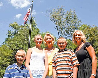 From left, Hunter Murcko, 7, Cassie Murcko, 12, and their grandmother Ruth Nilsson stand with Zachary Murcko, 11, and Amy Nilsson, in front of a flag pole memorial to Ruth's late husband, Gary, at Pioneer Pavilion in Mill Creek MetroParks.