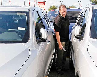 In this Aug. 11, 2011 photo, Jason Ashton looks at a new 2012 Dodge Durango at a dealership in Warren, Mich. Ashton, 38, of Shelby Township, Mich., plans to trade in his 2006 Dodge Ram pickup for a roomier SUV that will fit his wife, two kids and equipment. (AP Photo/Paul Sancya)