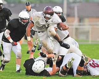Boardman running back #21 Devin Campbell hurdles over a would be Howland tackler during a scrimmage Friday night.