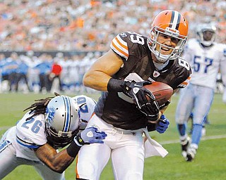 Cleveland Browns tight end Evan Moore (89) catches a 2-yard touchdown pass against Detroit Lions safety Louis Delmas (26) in the first quarter of an NFL preseason football game Friday, Aug. 19, 2011, in Cleveland. (AP Photo/Tony Dejak)