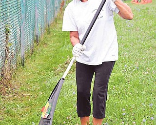 Cheryl Thompson, a special-education teacher at Taft Elementary, busily rakes the remains of weeds on and near school property.  About 35 volunteers took part in Saturday's Taft/Wilson Clean-up project, intended to beautify the neighborhoods surrounding Taft Elementary and Wilson Middle schools before students return to the classroom Aug. 29.