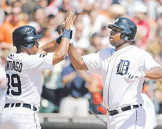Detroit Tigers' Delmon Young, right, is congratulated by Ramon Santiago after hitting a three-run home run against the Cleveland Indians in the third inning of a baseball game Sunday in Detroit. The Tigers won 8-7.