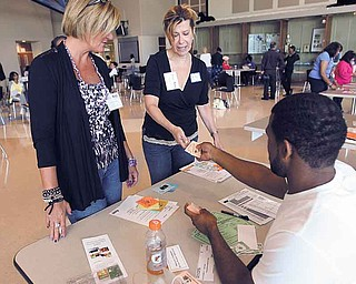 Martha Romine and Rita McNamara exchange cash for bus tickets with Malcom Horton on Monday during a Community Action Poverty Simulation at East High School. Participants, which included East High faculty, interacted with social-service agencies, grocers, police officers, pawnbrokers, bill collectors and prospective employers to get an idea of what low-income people go through.