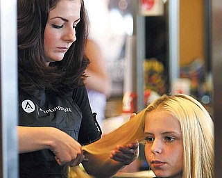 Rebekah Eastham of Wellsville starts cutting Britney Hallett's hair. The 16-year-old student from Youngstown was one of 30 kids who took part in the Angels For Kids' back-to-school make over at Casal's Aveda Institute, Austintown.