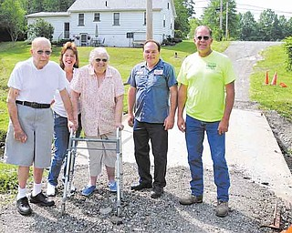 Haynie family members, from left, Walt, Grace and Betty and Jardine Building employees Bob Kolat and Eugene Macek stand in front of a damaged bridge that needs to be repaired. The bridge is the only access the Haynie family has to Niles-Vienna Road from their homes.
