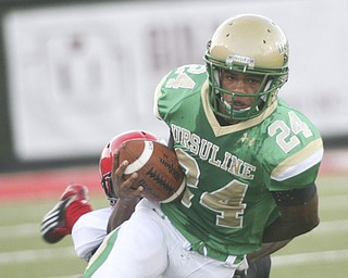 ROBERT K. YOSAY | THE VINDICATOR..BREAKIN AWAY -  Ursulines #24   Jermaine Williams  breaks away from  #50 Eli Ankou and #75 Danair Hardrick  as Ursulines #71 Ty Vasquez-Atkinsa  ..... for  a first down -- Youngstown Ursuline vs Red Lion  Christian Academy  at Stambaugh Stadium  Friday night. .----..... -30-