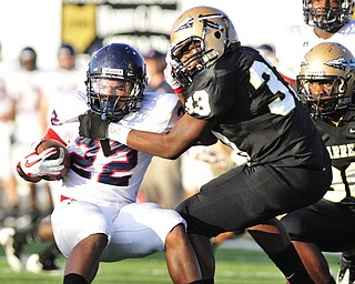 Austintown Fitch running back #22 Chris Davis tries to slip the tackle of Warren Harding's #33 Aundra'ez Cambridhge.