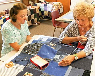 ROBERT K. YOSAY | THE VINDICATOR..Linda Spencer and Marlene Brocious  tie knots in the quilt --- Bethel Lutheran Church Piecemakers 425 Crestview Drive, off West Blvd. ---the women of the Piecemakers while they are making quilts to donate to Salvation Army..-30-