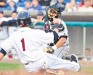 Base runner #1 Tony Wolters of Mahoning Valley slides into home plate before Jamestown catcher #12 Eddie Rodriguez.