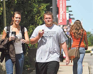 Kendal Malsch of Canfield, left, an early-childhood specialist major in her sophomore year at Youngstown State University, and Wes Wagner of Poland, a junior majoring in civil engineering, catch up as they walk down University Circle to class Monday, the first day of classes.