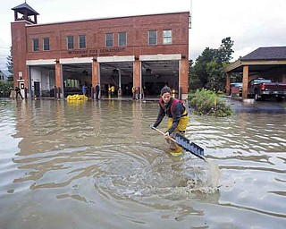 Firefighter Mandy Drake clears a storm drain in front of the fire department in Waterbury, Vt., in the wake of Irene on Monday.