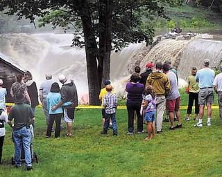 Residents watch as water rushes over the Ascutney Mill Dam on Kennedy's Pond in Windsor, Vt. A weakened but dangerous Tropical Storm Irene dumped up to half a foot of rain in places, flooded roads, knocked down trees and left more than 165,000 Vermont homes and businesses in the dark before blowing out of the state Sunday.