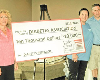 Jill Pupa, left, executive director of the American Diabetes Association in Cleveland, stands with Dr. Michelle Anania and Dr. Lawrence DiDomenico to display a mock check representing the $10,000 raised through the Ankle & Foot Care Centers' 13th annual golf benefit to support the association's work. The presentation followed the golf outing Aug. 15 at the Lake Club in Poland. The podiatrists have raised more than $100,000 for diabetes since they began the outing in 1999. Diabetes often causes severe foot pain and disabilities as a result of nerve and blood vessel damage.