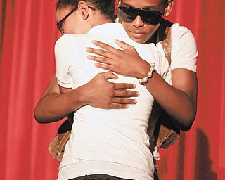 Chaney seventh-grader Mina Bonilla, celebrating her 12th birthday, gets a hug from Prodigy, 14, one of the four members of  Mindless Behavior. The quartet of 14-year-old pop, hip hop and R&B artists made a surprise stop Wednesday at the Youngstown  school.