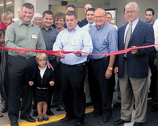 Save-A-Lot co-owner John Kawecki cuts the ribbon at the grand opening of the chain's newest location, on Gypsy Lane near Belmont Avenue on Youngstown's North Side. From left is co-owner Henry Nemenz Jr.; his son, Henry; Kawecki; Henry Nemenz Sr.; and Youngstown Mayor Charles Sammarone. The store is in the same location as the former Sparkle Market, which closed last year.