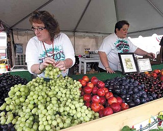 Ella Maria Guzzo-Welsh and Christina Guzzo perfect the fresh-fruit display their family has had for the more than 50 years at the Canfield Fair. Their stand is one of the health alternatives to traditional fair food, as is DiRusso's stand selling turkey sausage.