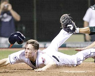 Cleveland Indians' Cord Phelps slides safely into home plate to score the game-winning run as Oakland Athletics catcher Kurt Suzuki is late on the tag in the 16th inning in a baseball game, early Thursday, Sept. 1, 2011, in Cleveland. The Indians won 4-3. (AP Photo/Tony Dejak)