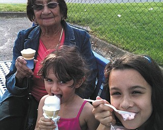 Catalina Lugo of Campbell is savoring ice cream from the Boardman Handel's with great-granddaughters Amaya and Aliya Abeid of New Middletown.