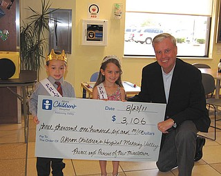 Cordell Hanley, known as Corey, 5, and Lillie Zoldan, 6, the prince and princess of New Middletown, present a check for Akron Children's Hospital Mahoning Valley to ACH President and Chief Executive Officer William Considine. Lillie, the daughter of Neal and Lesa Zoldan of New Springfield, and Corey, the son of Larry and Michelle Hanley of New Springfield, claimed their royal titles by raising the most funds for the hospital in July among contestants who sold lemonade, or had garage sales, neighborhood carnivals or other activities. They also served as grand marshals during the New Middletown National Night Out parade Aug. 2, and they will be making other public appearances throughout the community. The July fundraiser was coordinated by Kerri Bernard, Connie Brinker and Melissa Guzman, all of Hair Galleria in New Middletown.