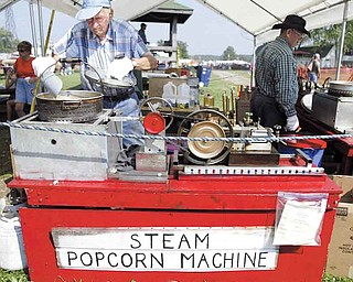 Thomas Hacon of Austintown makes popcorn at his booth at the Canfield Fair. The octogenarian has been making popcorn at the fair for nearly 20 years. His machine is powered by compressed air and LP gas, patterned after a steam machine he saw when he was a boy. He gives samples away.