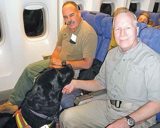 Paul Dostie, left, a retired investigator with the Mammoth Lake, Calif., Police Department, Buster, the cadaver dog he trained, and Dr. Donald K. Allen of Youngstown, are shown on their way to Tarawa, an atoll in the Pacific Ocean, to look for the remains of Americans declared missing in action in the battle with the Japanese in November 1943.