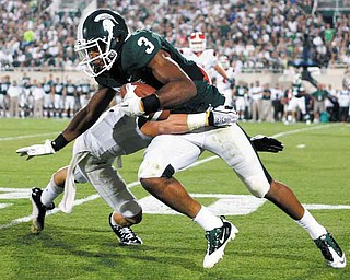 Michigan State's B.J. Cunningham (3) works for extra yardage on a pass reception against Youngstown State's Donald D'Alesio during the third quarter of an NCAA college football game, Friday, Sept. 2, 2011, in East Lansing, Mich. Cunningham caught nine passes for 130 yards and a touchdown. (AP Photo/Al Goldis)