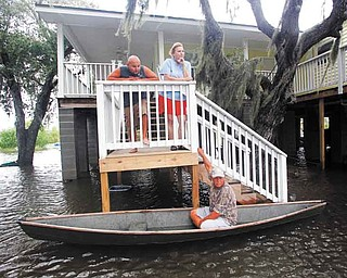 Ernie Adams sits in his pirogue while visiting his neighbors, Justin and Peggy Hatty, above, as they watch workers sandbag floodwaters from Bayou Barataria, seen in background, in the aftermath of Tropical Storm Lee in the town of Jean Lafitte, La., just outside New Orleans, Saturday, Sept. 3, 2011. (AP Photo/Gerald Herbert)