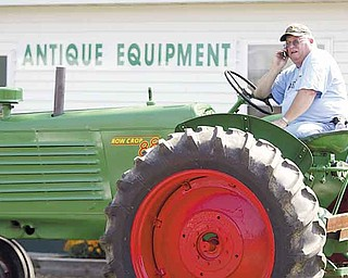 Earl Moracco of Ellsworth takes a break to make a phone call from atop his 1951 restored Oliver tractor in the antique farm-equipment exhibit at the 165th Canfield Fair.