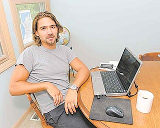 In this Sept. 2, 2011 photo, Ryan McGrath, 26, poses in his home in Michigan City, Ind. McGrath has been working part time designing web sites for small businesses but wants steadier full-time work. (AP Photo/Joe Raymond)