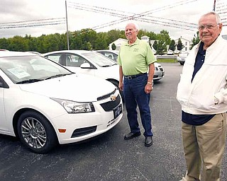 Bob Thomas, left, of North Jackson and Ray Milstead of Austintown talked Tuesday at the Spitzer Chevrolet dealership in North Jackson about driving their Chevrolet Cruzes. Thomas and Milstead each bought one of the first Cruzes last fall. The Lordstown-built car celebrates the anniversary of its launch Thursday.