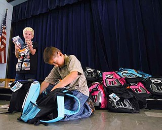 Watson Elementary third-graders Logan Swain, left, and Gage Nush check out what's inside their new bookbags. The bookbags were donated by United Way and will be given to more than 50 students at the school.