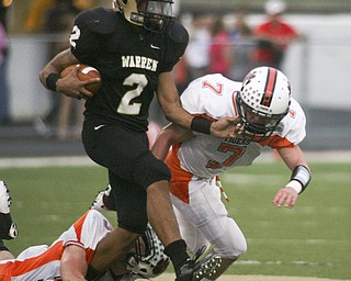 ROBERT  K.  YOSAY  | THE VINDICATOR --..Warrens #2 Jalyn Powell  tries to Break the tackle of #32 Dan Russell  and Howlands #7  Zach WIlson during first quarter action as they brought him down at the line  . Howland Tigers vs Warren G Harding Raiders @ Warren ..--30-..(AP Photo/The Vindicator, Robert K. Yosay)