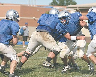 Anthony Pesce, second from right, rushes through the line at a recent Hubbard High School practice.