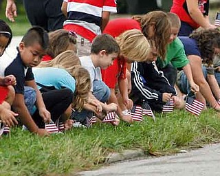 Second-graders place  flags along Stadium Drive to honor those who served their country.