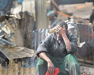 Joseph Mwangi, 34, sits in a state of shock after discovering the charred remains of two of his children, one aged 6, the other of unknown age, at the scene of a fuel explosion in Nairobi, Kenya, Monday, Sept. 12, 2011. A leaking gasoline pipeline in Kenya's capital exploded on Monday, turning part of a slum into an inferno in which at least 61 people were killed and more than 100 hurt. (AP Photo/Ben Curtis)