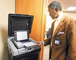 Raymond Butler, a Mahoning County Board of Elections employee, shows off the new paper-ballot voting system the county will use in the November general election.
