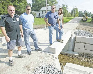 Grace Haynie, far right, stands on a bridge leading to her familyÕs property off Niles-Vienna Road. With her, from left, are Bob Kolat, Jeff Jardine and Eugene Macek of Jardine Builders and Septic System in Niles, which helped to replace an old bridge at the site..