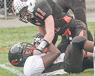 Canfi eld's Bryce Jackson (on bottom) battles for the ball with Howland's Dan Ebert (11) during Friday's game in Howland. The Tigers defeated the Cardinals, 30-28, on a 38-yard fi eld goal with 4.7 seconds left in the game.