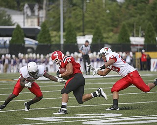JESSICA M. KANALAS | THE VINDICATOR..Youngstown's running back Jamaine Cook rushes for 5 yards and is then tackled by Illinois State's Austin Davis and Mike Banks during the second quarter...-30